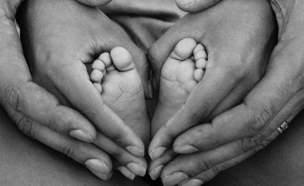 Photo en noir et blanc des pieds de bébé et des mains des parents.